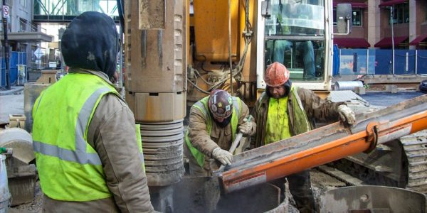Construction workers pouring concrete into a drilled shaft