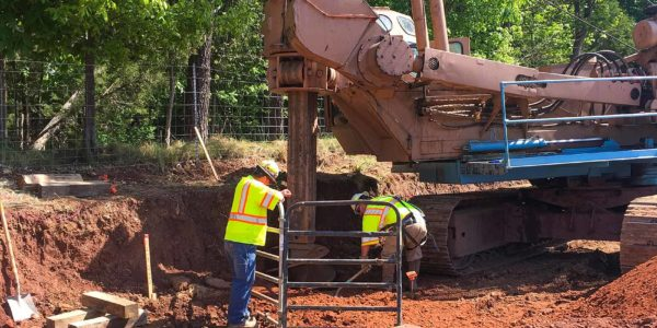 Closeup of construction workers drilling a foundation for a retaining wall